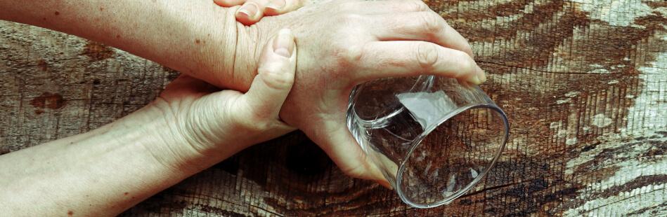 Erkrankten Personen zittern oftmals die Hände. Das alltägliche Leben erschwert sich auf diese Weise
